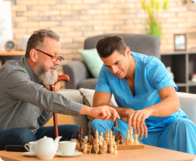 caregiver and elderly man playing chess