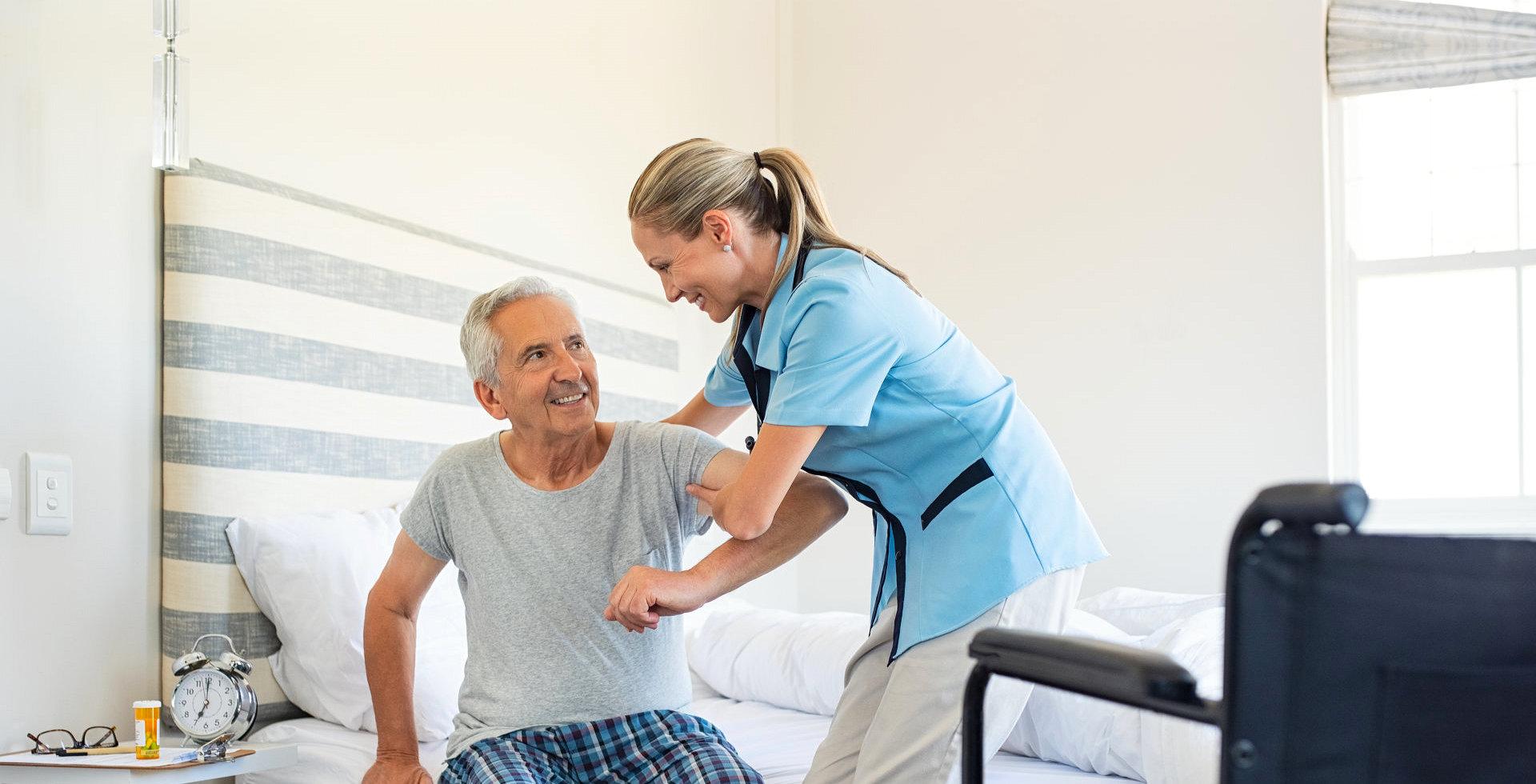 caregiver helping an elderly man