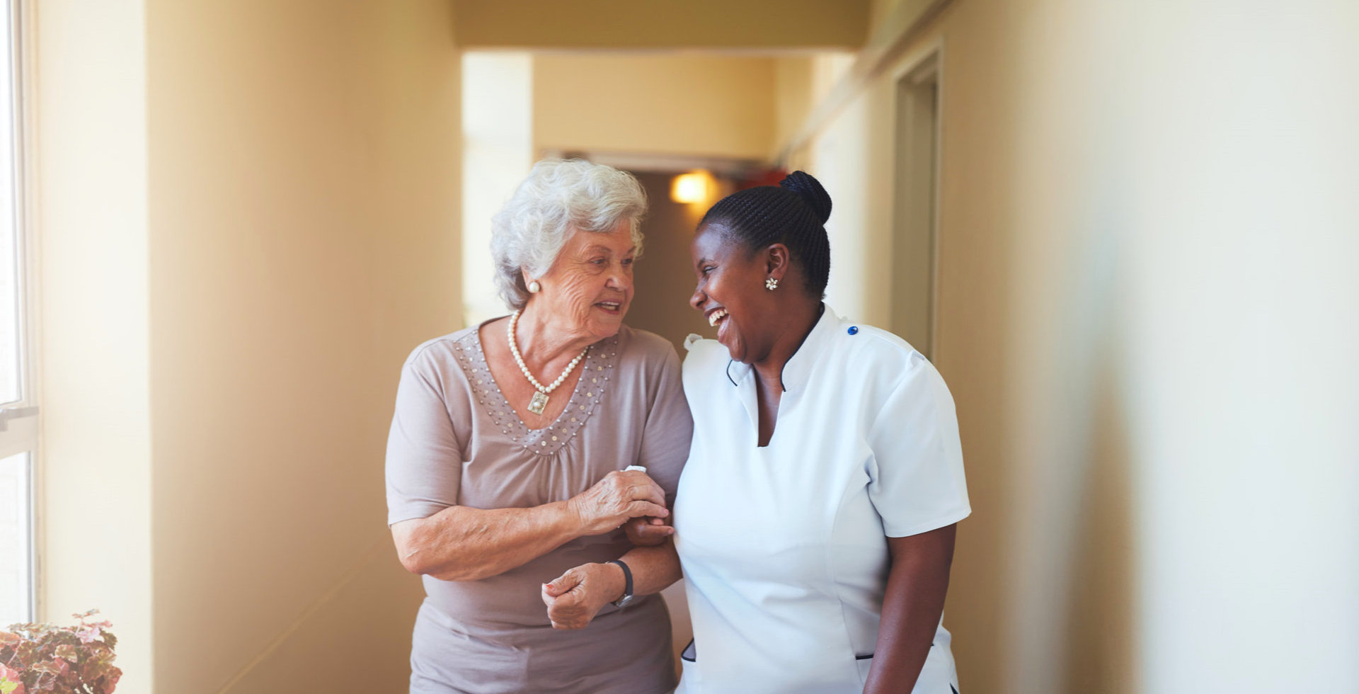 caregiver and elderly woman are walking