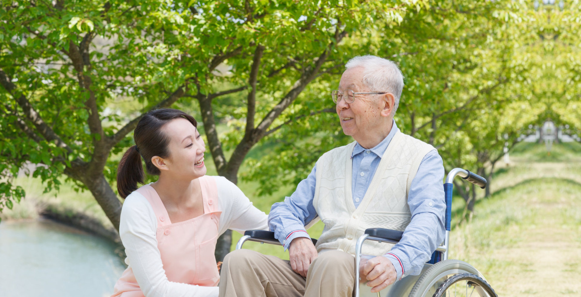 caregiver and elderly man smiling each other