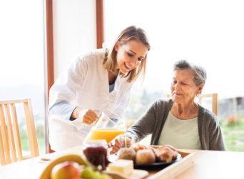 female caregiver serving juice to senior woman