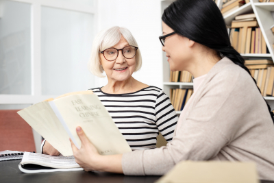 senior woman reading with adult woman