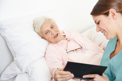 senior woman with caregiver in bed
