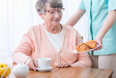 caregiver giving food to senior woman